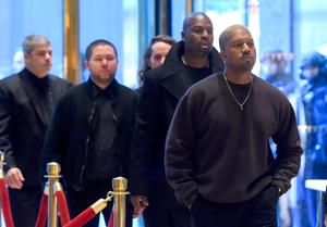 Singer Kanye West(R) arrives at Trump Tower December 13, 2016 as US President-elect Donald Trump continues to hold meetings In New York. / AFP / TIMOTHY A. CLARY        (Photo credit should read TIMOTHY A. CLARY/AFP/Getty Images)