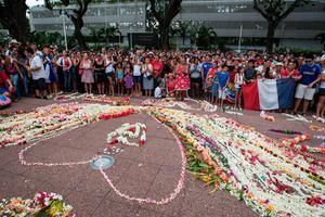 People gather at the Pouvanaa a Oopa Monument, in Papeete in front of the Assembly of French Polynesia, on November 15, 2015, to pay tribute to the victims of attacks in the French capital Paris on November 13, in which over 130 people died and more than 350 were injured. Hundreds of meters of flower garlands were made for the remembrance and a minute of silence was held. AFP PHOTO / GREGORY BOISYYGREGORY BOISSY/AFP/Getty Images