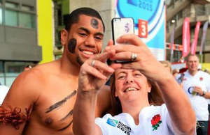 England fans take a photo with a man in Fijian dress before the Rugby World Cup match at Twickenham Stadium, London. PRESS ASSOCIATION Photo. Picture date: Friday September 18, 2015. See PA story RUGBYU England. Photo credit should read: Mike Egerton/PA Wire. RESTRICTIONS: Editorial use only. Strictly no commercial use or association without RWCL permission. Still image use only. Use implies acceptance of Section 6 of RWC 2015 T&Cs at: http://bit.ly/1MPElTL Call +44 (0)1158 447447 for further info.