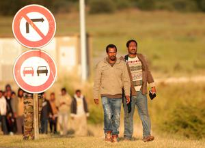 Migrants walk toward the Eurotunnel site at Coquelles in Calais, France. PRESS ASSOCIATION Photo. Picture date: Thursday July 30, 2015. Nine people have been killed attempting to cross the Channel in the last month, according to Eurotunnel, as migrants try to reach Britain. See PA story POLITICS Calais. Photo credit should read: Yui Mok/PA Wire