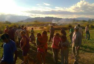 """People gather near the smoking remains of a helicopter that crashed with another near Villa Castelli in the La Rioja province of Argentina, Monday, March 9, 2015. Two helicopters carrying passengers filming the popular European reality show """"Dropped"""" crashed Monday in the remote area of northwest Argentina, killing everyone on board, authorities said. (AP Photo/Gabriel Gonzalez)"""