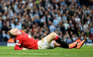 Manchester United's Wayne Rooney appears to be in discomfort after colliding with Manchester City's Joe Hart during the Barclays Premier League match at the Etihad Stadium, Manchester. Martin Rickett/PA Wire.