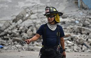 A rescue worker searches the rubble after a 7.8-magnitude quake in Gauyaquil, Ecuador on April 17, 2016.  At least 235 people were killed when a powerful earthquake struck Ecuador, destroying buildings and a bridge and sending terrified residents scrambling from their homes, authorities said Sunday. / AFP PHOTO / LUIS ACOSTALUIS ACOSTA/AFP/Getty Images