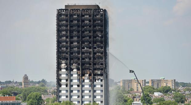 Firefighters spray water on to Grenfell Tower after the blaze in 2017 (Victoria Jones/PA)