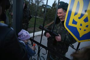 LUBIMOVKA, UKRAINE - MARCH 03:  A Ukrainian soldier at the Belbek military base talks with family members, including his daughter, through the gates of the base entrance on March 3, 2014 in Lubimovka, Ukraine. Tensions at the base, where between 100 and 200 Ukrainian soldiers are stationed, are high as a 4pm deadline reportedly given by Russian troops for the Ukrainians to surrender passed and locals feared the Russians might attack tonight. Heavily-armed soldiers who are not displaying identifying insignia but are widely believed to be Russians have blockaded several Ukrainian military bases across Crimea.  (Photo by Sean Gallup/Getty Images)
