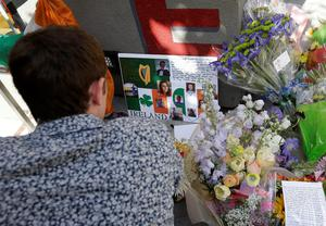 A man who did not give his name looks at photographs, cards and flowers from a shrine for victims from the Library Gardens apartment building balcony collapse in Berkeley (AP Photo/Jeff Chiu)