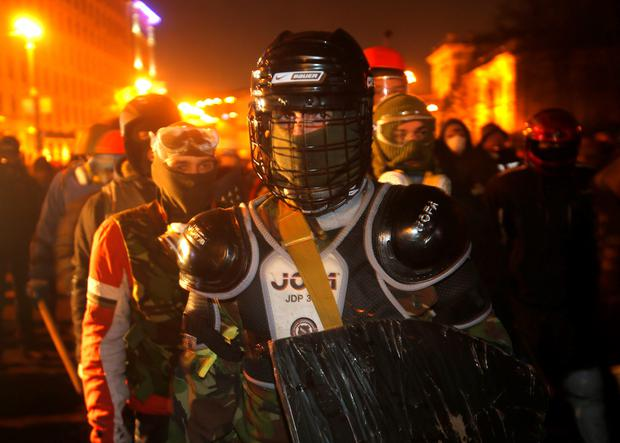 Protesters clad in improvised protective gear prepare for a clash with police in central Kiev, Ukraine, Monday, Jan. 20, 2014. After a night of vicious streets battles, anti-government protesters and police clashed anew Monday in the Ukrainian capital Kiev. Hundreds of protesters, many wearing balaclavas, hurled rocks and police responded with tear gas. (AP Photo/Sergei Grits)