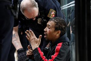 BALTIMORE, MD - APRIL 27:  A Baltimore Police officer checks on a man who was injured along Reisterstown Road near Mondawmin Mall during a protest April 27, 2015 in Baltimore, Maryland. A group of young protestors clashed with police in the streets near Mondawmin Mall in the afternoon following Freddie Gray's funeral. (Drew Angerer/Getty Images)