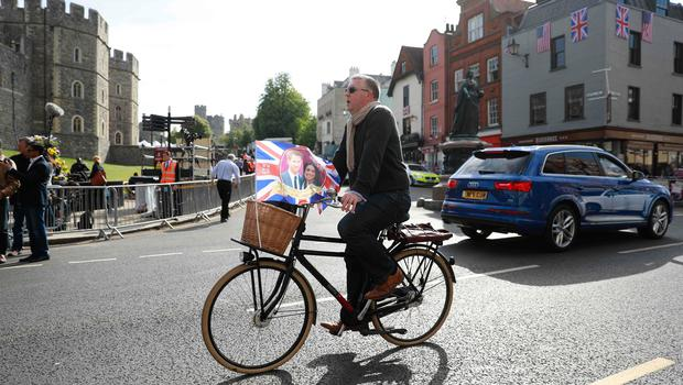 A man with a Royal Wedding souvenir flag rides a bicycle past Windsor Castle in Windsor on May 18, 2018, the day before the Royal wedding.  Britain's Prince Harry and US actress Meghan Markle will marry on May 19 at St George's Chapel in Windsor Castle. / AFP PHOTO / Odd ANDERSENODD ANDERSEN/AFP/Getty Images