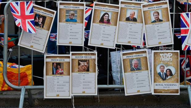 A picture shows Royal Family Top Trumps cards, a card game where you compare ratings and values to try to 'trump' and win your opponents card, showing (L-R) Britain's Catherine, Duchess of Cambridge, Britain's Prince William, Duke of Cambridge, and Britain's Prince Harry, hanging on a barrier in Windsor on May 18, 2018, the day before the Royal wedding of Prince Harry and Meghan Markle.  Britain's Prince Harry and US actress Meghan Markle will marry on May 19 at St George's Chapel in Windsor Castle. / AFP PHOTO / Paul ELLISPAUL ELLIS/AFP/Getty Images