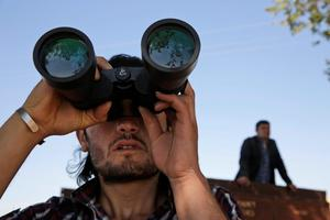 A Turkish Kurd, standing in the outskirts of Suruc, on the Turkey-Syria border, use binoculars to watch the fighting between militants of the Islamic State group and Kurdish forces in Kobani, Syria, Monday, Oct. 6, 2014. Kobani, also known as Ayn Arab and its surrounding areas have been under attack since mid-September, with militants capturing dozens of nearby Kurdish villages. (AP Photo/Lefteris Pitarakis)