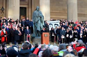 Former Liverpool player and manager Kenny Dalglish (C), stands at a podium as he reads a poem, on the steps of St George's Hall in Liverpool, north west England on April 27, 2016, in remembrance of the 96 Liverpool fans who died in the 1989 Hillsborough football stadium disaster. Thousands of sympathisers paid an emotional tribute to the Hillsborough disaster victims today after a landmark inquest found that 96 Liverpool football fans were unlawfully killed. / AFP PHOTO / PAUL ELLISPAUL ELLIS/AFP/Getty Images