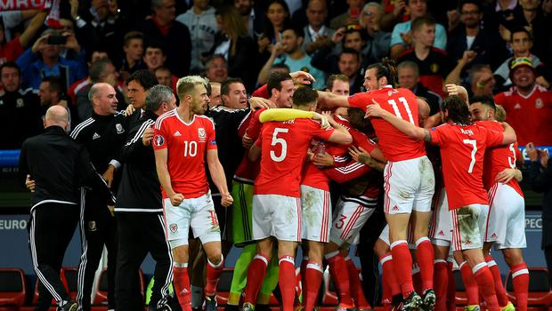 Wales' Hal Robson-Kanu (hidden) celebrates scoring his side's second goal of the game with coaching staff and players during the UEFA Euro 2016, quarter final match at the Stade Pierre Mauroy, Lille. PRESS ASSOCIATION Photo. Picture date: Friday July 1 2016. See PA story SOCCER Wales. Photo credit should read: Joe Giddens/PA Wire. RESTRICTIONS: Use subject to restrictions. Editorial use only. Book and magazine sales permitted providing not solely devoted to any one team/player/match. No commercial use. Call +44 (0)1158 447447 for further information.