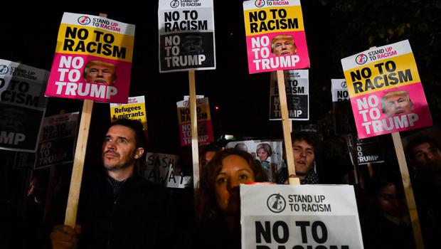 "Demonstrators hold placards that read ""No to racism, no to Trump"" during a protest outside the US Embassy in London on November 9, 2016 against US President-elect Donald Trump after he was declared the winner of the US presidential election.  Political novice and former reality TV star Donald Trump has defeated Hillary Clinton to take the US presidency, stunning America and the world in an explosive upset fueled by a wave of grassroots anger. / AFP PHOTO / BEN STANSALLBEN STANSALL/AFP/Getty Images"