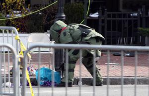 BOSTON, MA - APRIL 15:  A member of the bomb squad investigates a suspicious item on the road near Kenmore Square after two bombs exploded during the 117th Boston Marathon on April 15, 2013 in Boston, Massachusetts. Two people are confirmed dead and at least 23 injured after two explosions went off near the finish line to the marathon.  (Photo by Alex Trautwig/Getty Images)