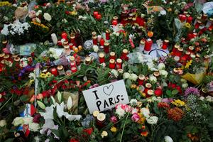 "BERLIN, GERMANY - NOVEMBER 16:  A hand-written message reads: ""I love Paris"" among candles, messages and flowers left by mourners outside the French Embassy commemorating the victims of last Friday's terrorist attacks in Paris that have left over 130 people dead on November 16, 2015 in Berlin, Germany. Police are feverishly tracking down leads across Europe and looking for one of the attackers they think is still alive and on the run. The Islamic State (IS) has claimed responsibility for the attacks that were carried out by at least eight terrorists.  (Photo by Sean Gallup/Getty Images)"