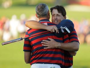 United States' Phil Mickelson hugs United States' Matt Kuchar after winning their match on the 17th hole during a four-ball match at the Ryder Cup golf tournament Saturday, Oct. 1, 2016, at Hazeltine National Golf Club in Chaska, Minn. (AP Photo/Charlie Riedel)