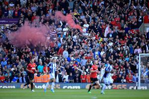 WEST BROMWICH, ENGLAND - MAY 19:  Manchester United fans light a flare during the Barclays Premier League match between West Bromwich Albion and Manchester United at The Hawthorns on May 19, 2013 in West Bromwich, England.  (Photo by Richard Heathcote/Getty Images)