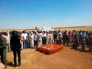 "Coffins of migrants and of Aylan Kurdi (also know as Aylan Shenu), a three-year-old boy whose drowning off Turkey, are pictured during a funeral ceremony in Kobane, on September 4, 2015 in Sanliurfa. ""Aylan Shenu, his brother, and his mother were buried today in Kobane in front of a large crowd. Everyone was very sad and crying,"" said local journalist Mustefa Ebdi, who attended the funeral service. AFP PHOTO / STRINGERSTR/AFP/Getty Images"