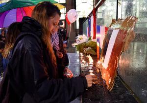 People light candles at a vigil held by the local French community in Sydney on November 14, 2015, as Australians express their solidarity with France following a spate of coordinated attacks that left 128 dead and 180 injured in Paris late on November 13. Both the Opera House and the Sydney Town Hall were bathed in the French colours and New South Wales state Premier Mike Baird said he had also asked for a French flag to fly over the city's famous harbour bridge. AFP/Getty Images