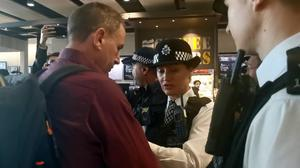 James Brown, a former Paralympian, being detained by police following his protest by flying a drone near Heathrow Airport (Caitlin Doherty/PA)