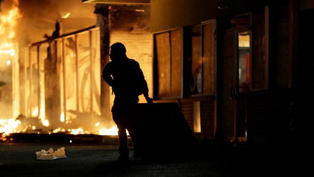 A man watches as stores burn Tuesday, Nov. 25, 2014, in Ferguson, Mo. A grand jury has decided not to indict Ferguson police officer Darren Wilson in the death of Michael Brown, the unarmed, black 18-year-old whose fatal shooting sparked sometimes violent protests. (AP Photo/David Goldman)