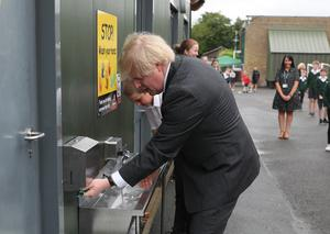Boris Johnson uses a sink in the playground to wash his hands during a visit to Bovingdon Primary School in Hemel Hempstead (Steve Parsons/PA)