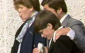 Gavin Larmour as a heartboken youngster at the funeral of dad John