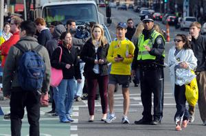 BOSTON, MA - APRIL 15:  A police officer directs people around the finish line at the corner of Boylston Street and Massachusetts Avenue after two explosives detonated during the 117th Boston Marathon on April 15, 2013 in Boston, Massachusetts. Two people are confirmed dead and at least 28 injured after at least two explosions went off near the finish line to the marathon.  (Photo by Darren McCollester/Getty Images)