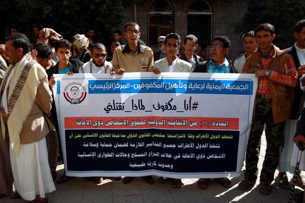 Yemeni blind men hold a banner during a demonstration gathering disabled people to protest after a centre for the blind was reportedly destroyed by Saudi-led airstrikes in the capital Sanaa on January 6, 2016. AFP/Getty Images