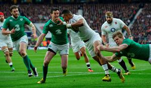 England's wing Anthony Watson (C) gets tackled during the Six Nations international rugby union match between England and Ireland at Twickenham in south west London on February 27, 2016.   / AFP / GLYN KIRKGLYN KIRK/AFP/Getty Images