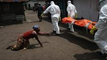 A woman crawls towards the body of her sister as Ebola burial team members take her sister Mekie Nagbe, 28, for cremation on October 10, 2014 in Monrovia, Liberia.  (Photo by John Moore/Getty Images)