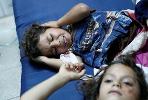 Palestinian children, wounded in an Israeli strike on a compound housing a U.N. school in Beit Hanoun, in the northern Gaza Strip, are treated as they lay on the floor at the emergency room of the Kamal Adwan hospital in Beit Lahiya, Thursday, July 24, 2014. (AP Photo/Lefteris Pitarakis)