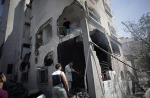 Palestinian inspect damages of their home which caught on fire following an Israeli strike that hit the next-door Hamas movement's Al-Aqsa satellite TV station in Gaza City, Thursday, July 31, 2014. (AP Photo/Khalil Hamra)