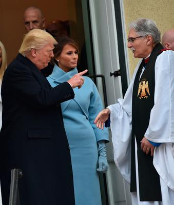 US President-elect Donald Trump and his wife Melania speak with Reverend Luis Leon as they leave St. John's Episcopal Church on January 20, 2017, before Trump's inauguration.  / AFP PHOTO / Nicholas KammNICHOLAS KAMM/AFP/Getty Images