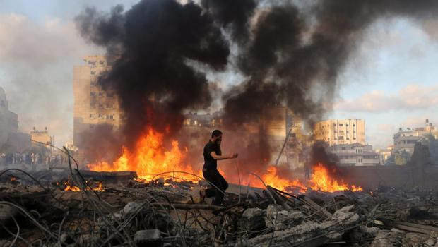 A Palestinian runs in an area damaged in an Israeli airstrike in Gaza City in the Gaza Strip on Thursday, July 24, 2014.  (AP Photo/Hatem Moussa)