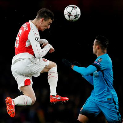 Arsenal's French defender Laurent Koscielny (L) heads the ball past Barcelona's Brazilian forward Neymar during the UEFA Champions League round of 16 1st leg football match between Arsenal and Barcelona at the Emirates Stadium in London on February 23, 2016.   / AFP / ADRIAN DENNISADRIAN DENNIS/AFP/Getty Images