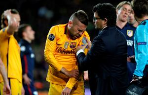 Barcelona's Jordi Alba, center, grimaces after injuring himself during a Champions League quarter-final, first leg soccer match between FC Barcelona and Atletico Madrid at the Camp Nou stadium in Barcelona, Spain, Tuesday April 5, 2016. (AP Photo/Emilio Morenatti)