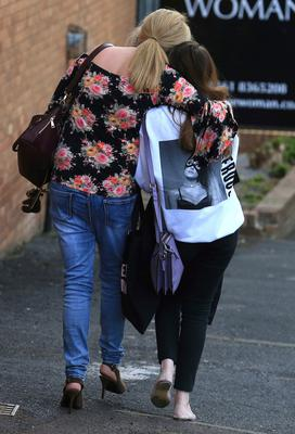 A fan is comforted as she leaves the Park Inn hotel in central Manchester, England Tuesday May 23 2017. Over a dozen people were killed in an explosion following a Ariana Grande concert at the Manchester Arena late Monday evening. (AP Photo/Rui Vieira)