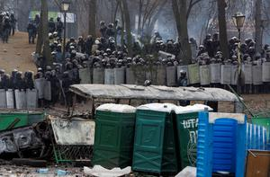 Protesters clash with police in central Kiev, Ukraine,  Monday, Jan. 20, 2014. Protesters erected barricades from charred vehicles in central Kiev as the sound of stun grenades pierce the freezing air, after a night of rioting sparked by passage of laws aims at curbing street protests. (AP Photo/Sergei Chuzavkov)