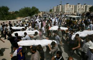 Palestinians carry bodies of 10 members of the Al Astal immediate and extended family, killed by an Israeli strike early at their houses, during their funeral in Khan Younis, in the southern Gaza Strip, Wednesday, July 30, 2014. (AP Photo/Eyad Baba)
