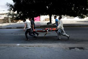 Palestinians carry a man on a strecher to an ambulance following an Israeli Strike in Shijaiyah neighborhood, eastern Gaza City, Wednesday, July 30, 2014. (AP Photo/Adel Hana)
