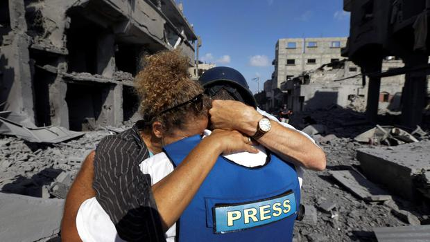 A member of the foreign media, left, cries as she embraces her Palestinian news assistant, right, who burst into tears after discovering his family house was destroyed by Israeli strikes in Beit Hanoun, northern Gaza Strip, Saturday, July 26, 2014. (AP Photo/Lefteris Pitarakis)