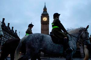 Horses canter past the Elizabeth Tower (more commonly known as Big Ben) and the Houses of Parliament in London on March 8, 2017, ahead of the government's Spring Budget announcement.
