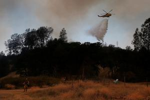 CLEARLAKE, CA - AUGUST 03:  A firefighting helicopter drops water on a spot fire along highway 20 during a backfire operation to head off the Rocky Fire on August 3, 2015 near Clearlake, California. Nearly 3,000 firefighters are battling the Rocky Fire that has burned over 60,000 acres has forced the evacuation of 12,000 residents in Lake County. The fire is currently 12 percent contained and has destroyed at least 14 homes. 6,300 homes are threatened by the fast moving  blaze.  (Photo by Justin Sullivan/Getty Images)