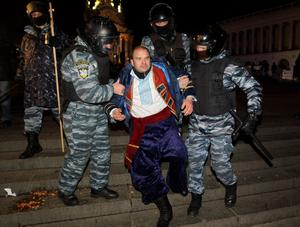 Ukrainian riot police officers detain an activist during a rally demanding the resignation of President Viktor Yanukovych, at the Independence Square in downtown Kiev, Ukraine, on Saturday, Nov. 30, 2013. Police in the Ukrainian capital broke up an anti-government demonstration in the city center before dawn Saturday, swinging truncheons and injuring many.  (AP Photo/Sergei Chuzavkov)