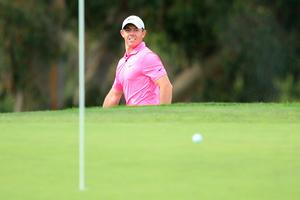 Keen eye: Rory McIlroy watches his shot from the bunker on the 13th hole