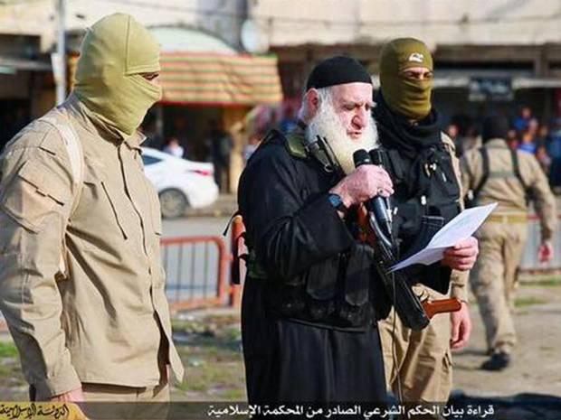 ISIS militants read out charges to a crowd before murdering men for being gay