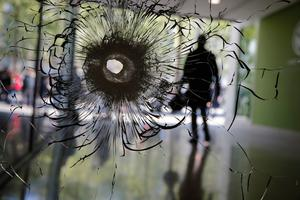 A bullet hole is pictured on a shopwindow of the Champs Elysees boulevard in Paris, Friday, April 21, 2017.