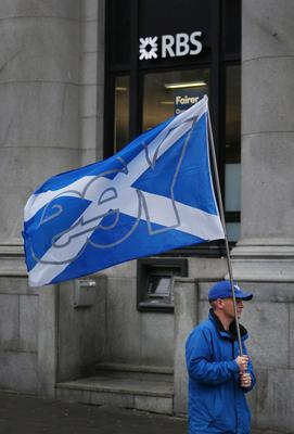 ABERDEEN, SCOTLAND - SEPTEMBER 15:  A yes campaigner passes a branch of the Royal Bank of Scotland (RBS) on September 15, 2014 in Aberdeen,Scotland. The latest polls in Scotland's independence referendum put the No campaign back in the lead, the first time they have gained ground on the Yes campaign since the start of August.  (Photo by Peter Macdiarmid/Getty Images)